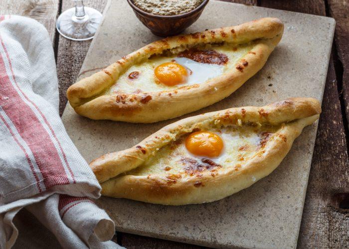 Two ajarian khachapuri, georgian bread with cheese and yolk.