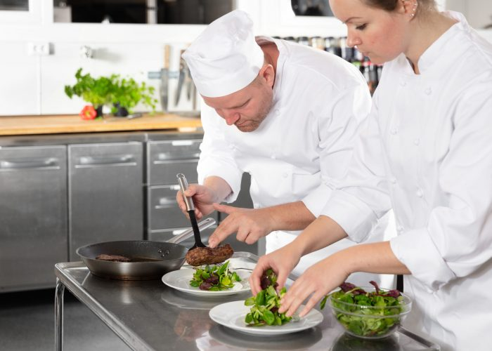 Two rofessional chefs prepares beef meat dish in a professional kitchen at gourmet restaurant or hotel.